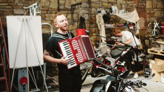 A photograph of While She Sleeps and an accordion