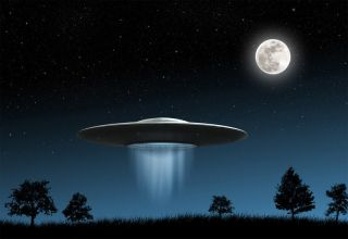 A UFO, or flying saucer, above a dark city and under a full moon.