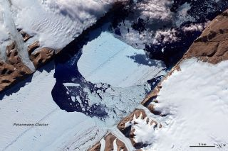 Large iceberg drifts away from Petermann Glacier ice shelf in Greenland.