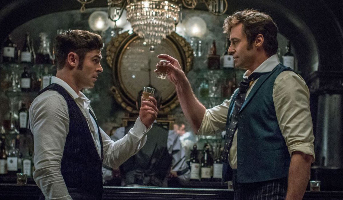 Zac Efron and Hugh Jackman toast with shots in The Greatest Showman.