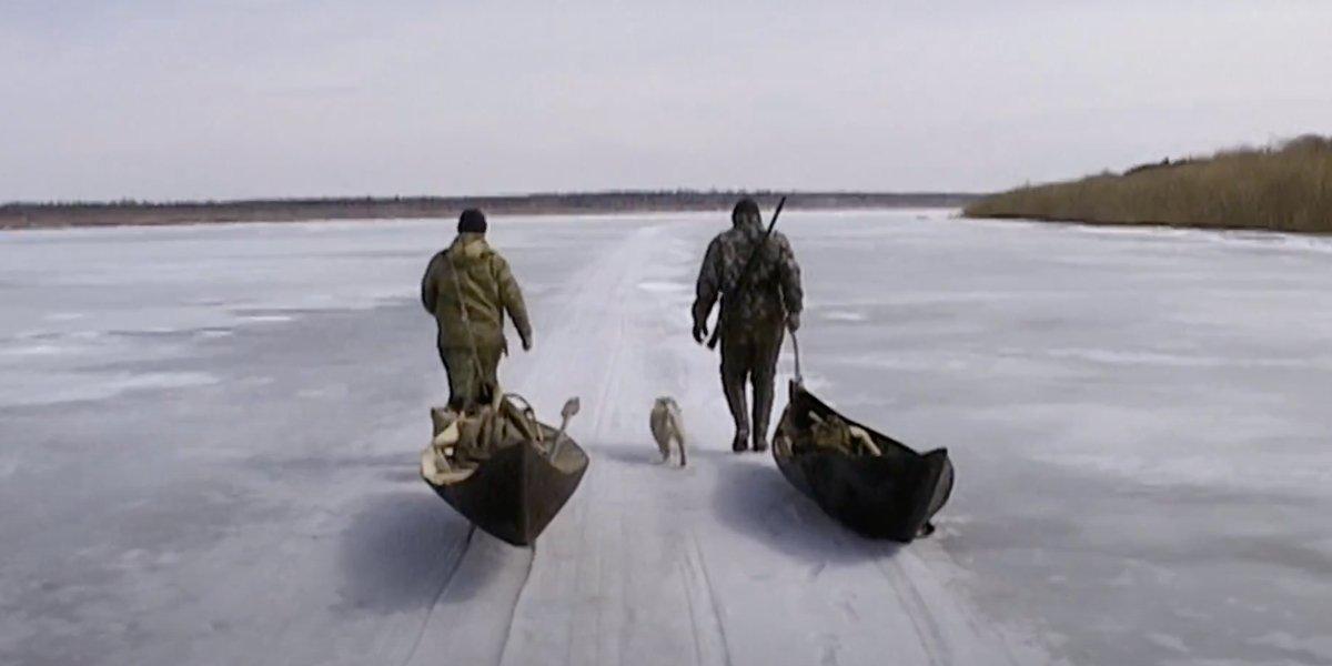 Two trappers walk along a frozen lake in Happy People