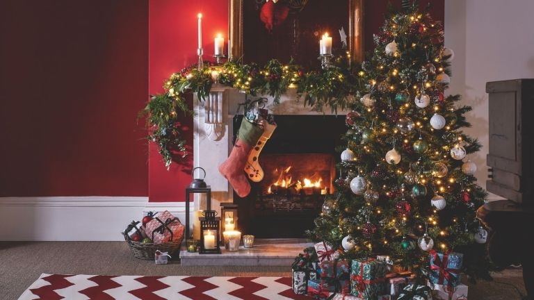 A Christmas tree in a home decorated Christmas tree decorating ideas, by a traditional fireplace in candlelight.