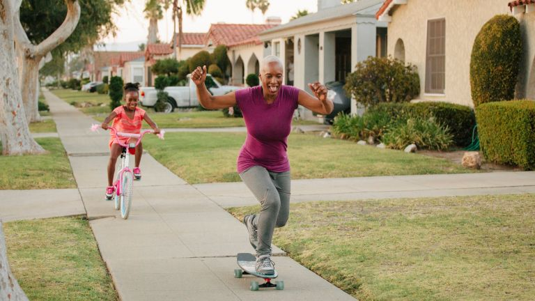Woman on skateboard doing unconventional workout with daughter