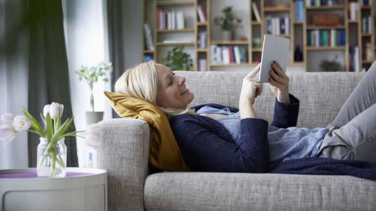 Woman lying on sofa looking at tablet