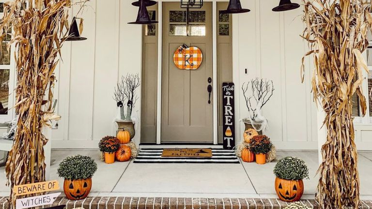 Halloween outdoor decor ideas with sage painted front door, gingham check pumpkin plaque pumpkin planters and floating witches hats