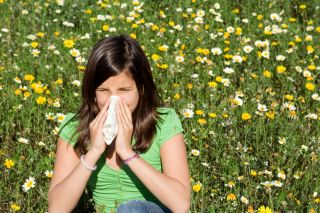 A woman sits near a field of flowers, blowing her nose.