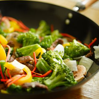 A wok holds a stir-fry with vegetables