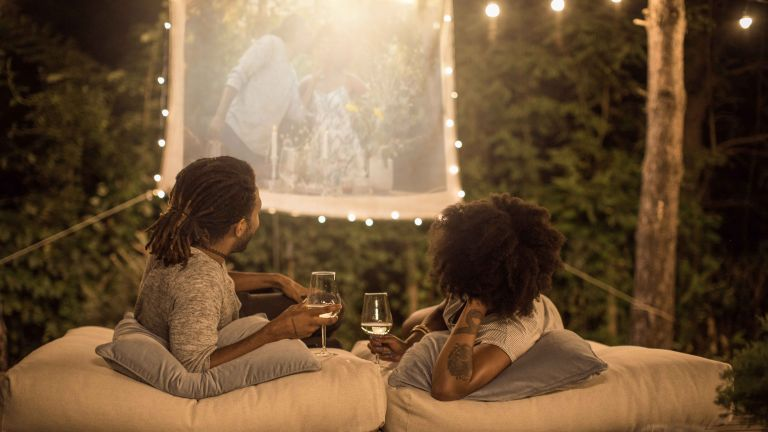 Outdoor projector in use in garden with couple laying on floor