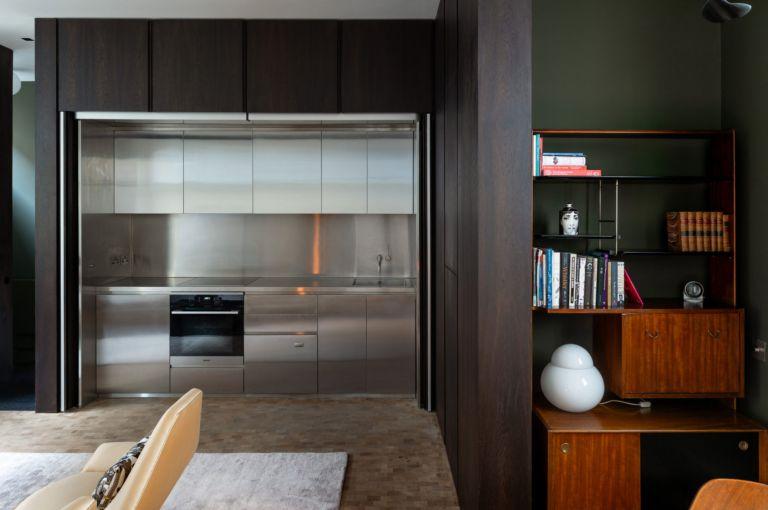 Open invisible kitchen with dark wooden doors