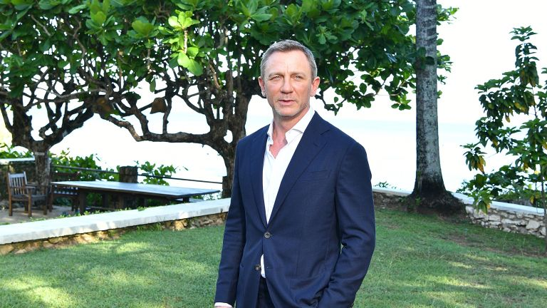 Daniel Craig poses for a photo dressed smartly in a garden