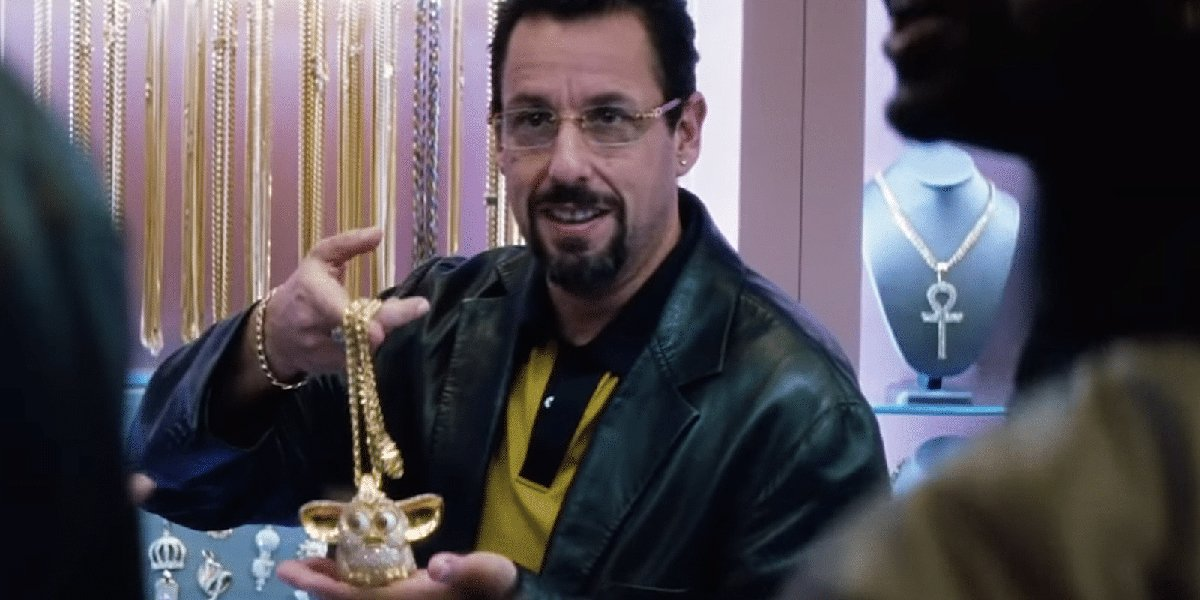 Adam Sandler holding a Furby necklace in Uncut Gems