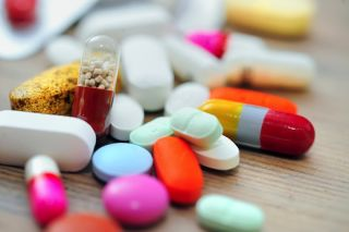 A pile of pills of various shapes and colors.