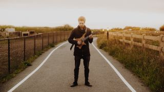Guitarist Plini poses with his guitar in the middle of a road