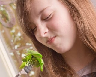 A little girl wrinkles her nose at the sight of eating veggies.