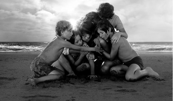 Roma the family huddles together on the beach