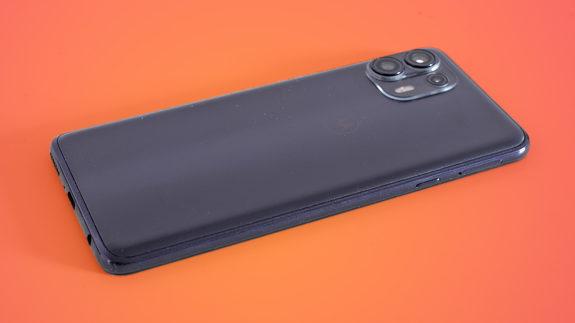 A Motorola Edge 20 Lite from the back against an orange background