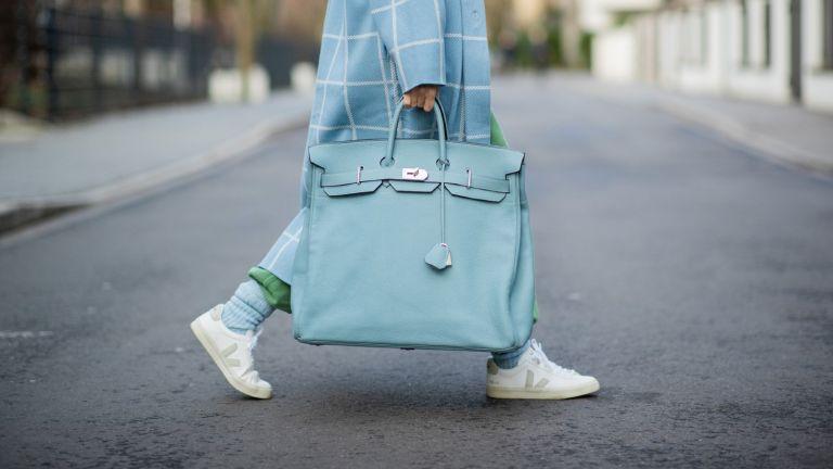 Woman carrying designer bag HERMÈS Birkin travel bag 40 in light blue