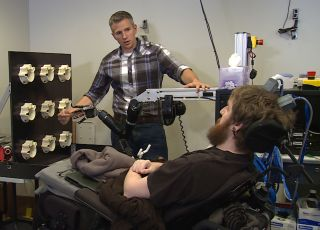 Researcher Rob Gaunt prepares Nathan Copeland for brain computer interface sensory test.