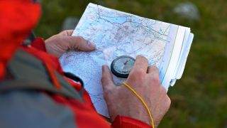 Best compasses: a man studying a map with a compass