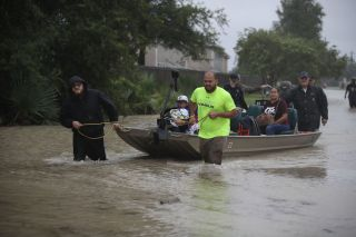 People in Houston walk down a flooded street on Aug. 28, 2017 as Tropical Storm Harvey drives them out of their homes.
