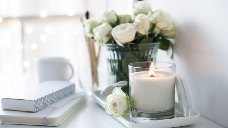 White room interior decor with burning hand-made candle and bouq - stock photo