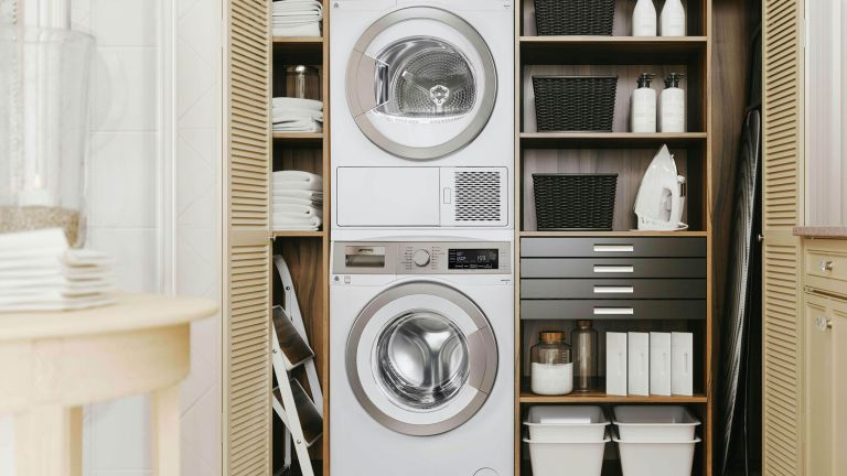 shelving in cream fitted inbuilt cabinets with washing machine and tumble dryer in a laundry room design -smeg