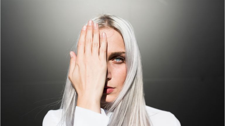 Portrait of serious young woman covering one eye - stock photo