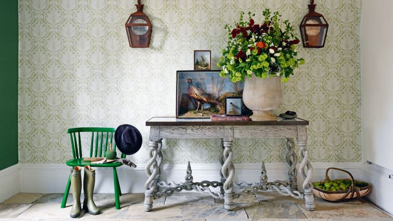 Entry table decor ideas with grey table, green wallpaper, flowers and paintings of pheasants