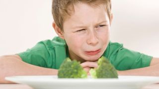 a young child sits at a table behind a plate of broccoli and looks grossed out