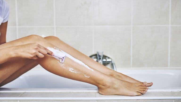 Woman shaving leg in bathroom using a razor