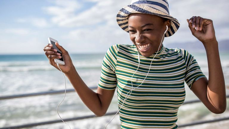 Do you check your sunscreen expiration? A young woman with a striped sunhat and stripey breton top stands in the sunshine listening to music