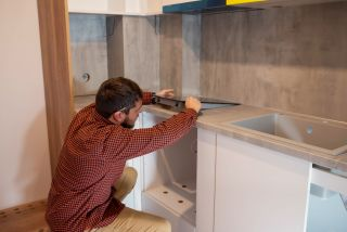 a worker fitting a kitchen with an induction hob