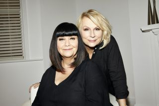 French & Saunders: Funny Women - Dawn French and Jennifer Saunders pose side-by-side and smiling in the 'White Room' set used on French & Saunders