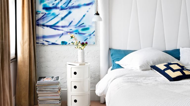 White bedroom with blue artwork and exposed brick wall painted white