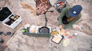 A camper tucking into food in a food container
