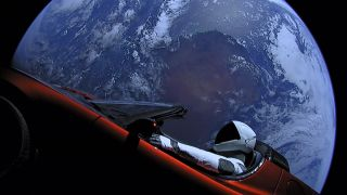 Image of Tesla Roadster and Starman dummy astronaut in space, looking down on the Earth
