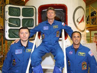 Spaceflyers Sergei Revin, Gennady Padalka and Joe Acaba pose in front of their Soyuz spacecraft