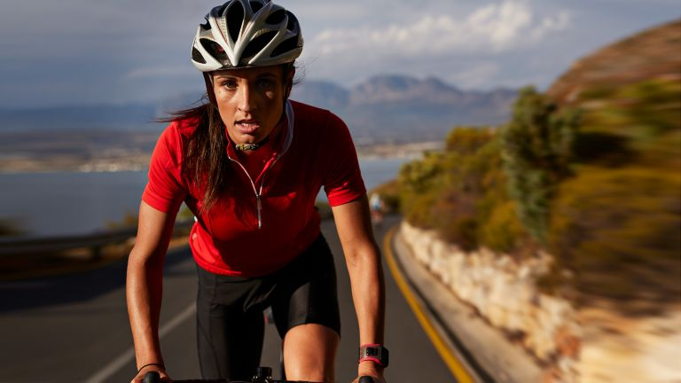 Woman road cycling up a hill