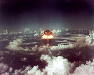 a photo of the detonation of an atoll during operation ivy in 1952, showing a mushroom cloud above the sea