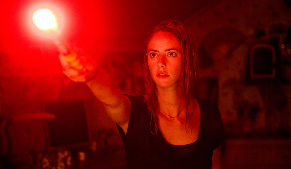 Kaya Scodelario holding out a flare in Crawl