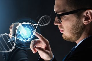 A man looks at a computer image of DNA.
