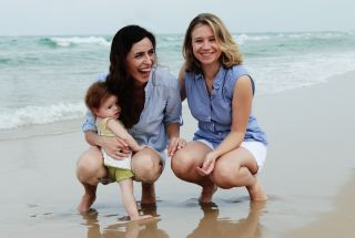 Lesbian couple and baby on beach