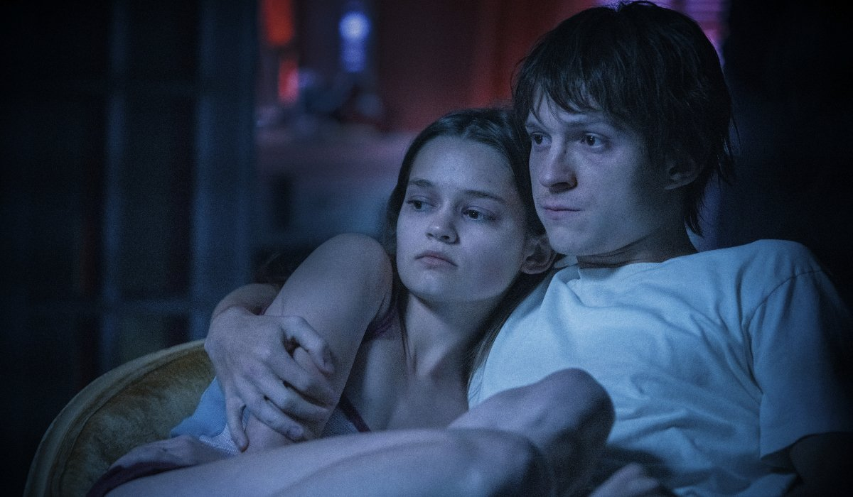 Ciara Bravo and Tom Holland getting close on the couch in Cherry