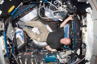 NASA astronaut Scott Kelly is pictured in the windowed cupola of the International Space Station in October 2010. He will return to the space station for a yearlong mission in March 2015.