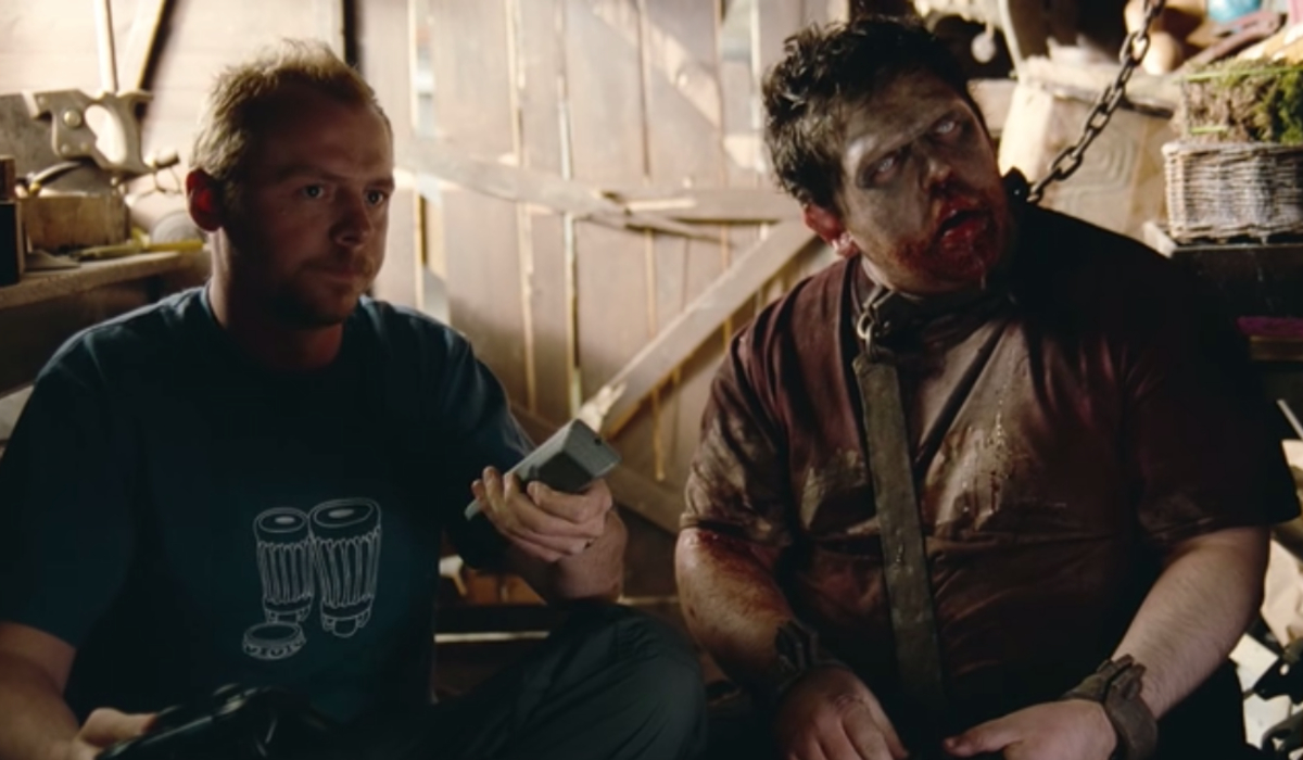 Shaun turns on the TV next to zombie Ed in Shaun of the Dead.