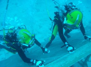 During a training session for the NEEMO 15 mission, planetary scientist Steve Squyres (left) and Japanese astronaut Takuya Onishi (right) get familiarized with the underwater asteroid simulation wall.
