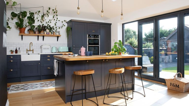 Dark blue Shaker kitchen with wood and black metal bar stools, black bifold doors and bare bulb lights over island
