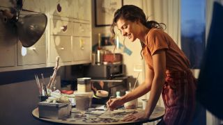 best website builder for artists: Smiling woman painting at desk