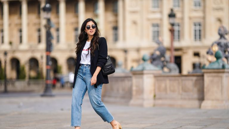 "Camille Grandguillote wears sunglasses, a black blazer jacket from Sezane, a black leather bag from Kate Lee, a white t-shirt from ""Pas le Time"", blue denim jeans pants from Asos, Chanel beige and black slingback shoes, on February 25, 2021 in Paris, France"