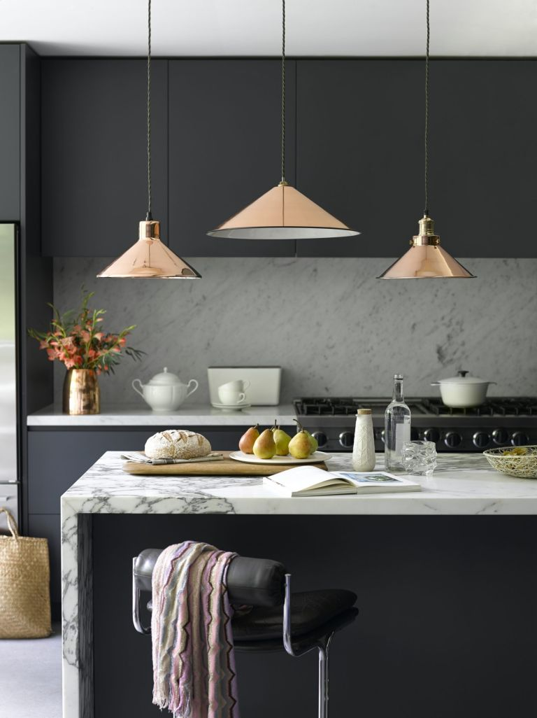 An example of lighting ideas for small kitchens showing copper pendant lighting over a kitchen island with a marble worktop